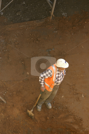 Builder and shovel stock photo, A workman leans on his shovel in a dirt pit by Leah-Anne Thompson