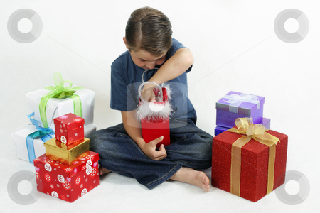 Christmas Fun stock photo, Boy opening presents on Christmas day. Gifts scattered around him. by Leah-Anne Thompson
