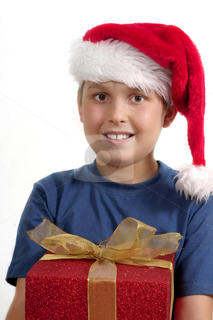 Christmas Giving stock photo, Child in blue shirt and red hat holding a red gift with gold ribbon. by Leah-Anne Thompson