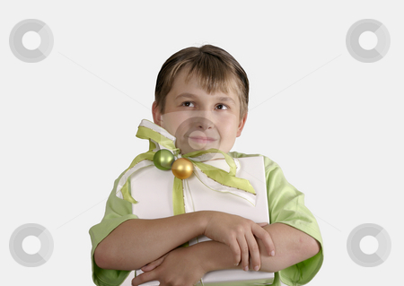 Child holding a wrapped present and thoughtfully looking up stock photo, Wishful Thinking.   Thoughtful child holding a wrapped present.  Space for copy. by Leah-Anne Thompson