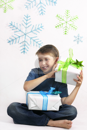 Christmas time stock photo, Boy holding ribbon tied gits on a hanging plastic snowflake background by Leah-Anne Thompson
