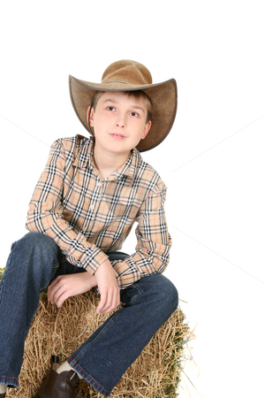 Boy looking up stock photo, Boy sitting on a hay bale and wearing country clothing, is looking up with expectation by Leah-Anne Thompson