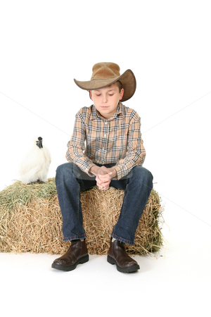 Country boy sitting on lucerne bale stock photo, A country boy sitting on a bale of lucerne hay thinks quietly. by Leah-Anne Thompson