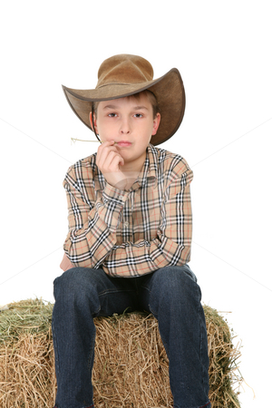 Cowboy sitting on hay bale stock photo, A child sits on  a bale of lucerne and casually chews on a piece. by Leah-Anne Thompson