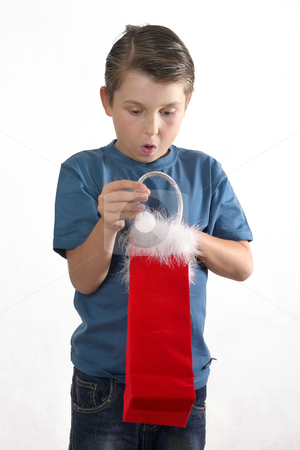 What's Inside stock photo, Curious boy looking inside a gift bag. by Leah-Anne Thompson