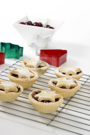 Christmas Baking stock photo, Small fruit pies with star decorations sitting on a wire cooler.  Focus on foreground. by Leah-Anne Thompson