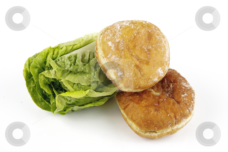 Salad Lettace and Jam Doughnut stock photo, Contradiction between healthy food and junk food using a green salad lettace and jam doughnut on a reflective white background by Keith Wilson