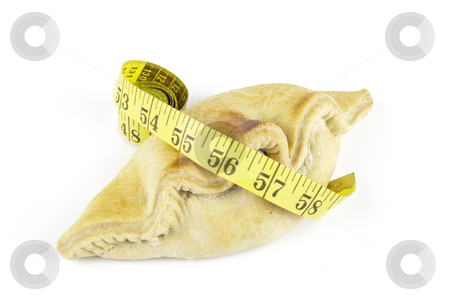 Pasty and Tape Measure stock photo, Single golden pasty and yellow tape measure on a reflective white background by Keith Wilson