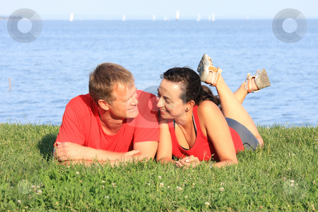 Young couple stock photo, Joyful young pair is overlapping shore of the lake by ARPAD RADOCZY