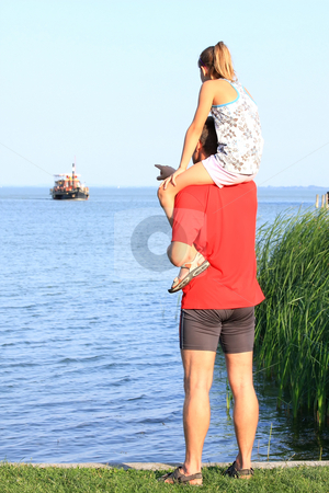 Family stock photo, A young father looks at the sailboats with his girls by ARPAD RADOCZY