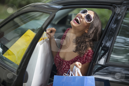 Young Woman Shopping stock photo, Young woman getting out of car holding shopping bags. Horizontally framed shot. by Edward Bock