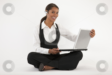 Young Woman Using Laptop and Blue Tooth stock photo, Young woman sitting on floor using laptop and wearing blue tooth headset. Horizontally format. by Edward Bock
