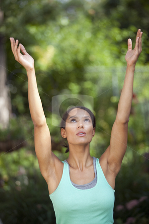 Young Woman Exercising stock photo, Young woman with arms raised in outdoor setting. Vertically framed shot. by Edward Bock