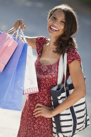 Young Woman Shopping stock photo, Young woman with shopping bags. Vertically framed shot. by Edward Bock