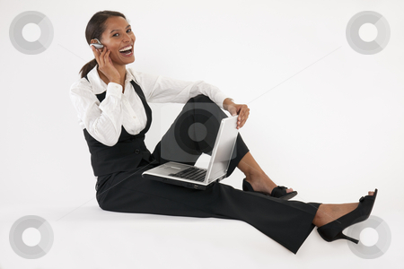 Young Woman Using Laptop and Blue Tooth stock photo, Young woman sitting on floor using laptop and wearing bluetooth headset. Horizontally format. by Edward Bock