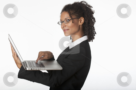 Young Businesswoman Using Laptop stock photo, Young businesswoman in profile using laptop. Horizontally framed shot. by Edward Bock