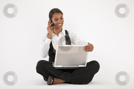 Young Woman Using Laptop and Cell Phone stock photo, Young woman sitting on floor using laptop and cell phone. Horizontally format. by Edward Bock