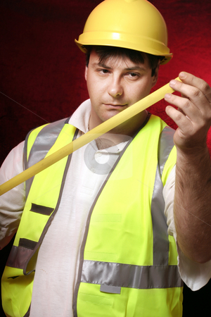 Measure up stock photo, Builder with his trusty tape measure on a black/red background by Leah-Anne Thompson