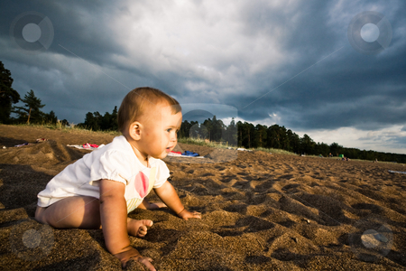 On a beach stock photo, Cute baby sitting on a beach under the thunder sky by Alexandr Vikulov