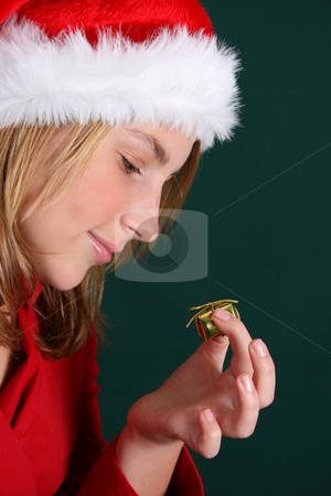 Christmas Present stock photo, Teenager in red holding a golden gift in her hand by Vanessa Van Rensburg