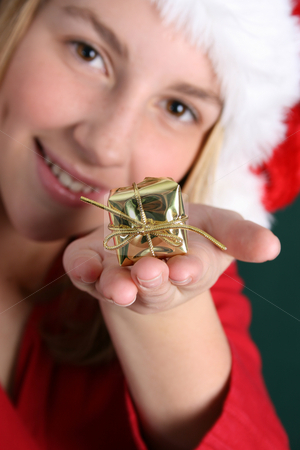 Christmas Present stock photo, Teenager in red holding a golden gift in her hand. FOCUS ON GIFT by Vanessa Van Rensburg