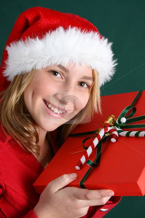 Christmas Present stock photo, Teenager wearing a christmas hat, holding a present by Vanessa Van Rensburg