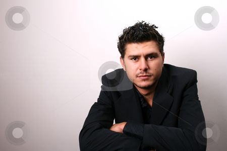 Male Model in Dark Lighting stock photo, Male model in studio against white wall by Vanessa Van Rensburg