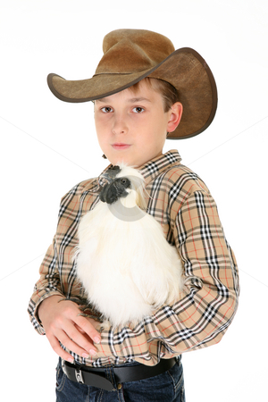 Country boy holding a chicken stock photo, A rural boy carrying a silkie chicken in his arms.  Silkie Bantams are excellent birds to keep as a pet. They are quite gentle and adapt well to human handling. The Silkie bantam is docile by nature and craves attention. by Leah-Anne Thompson