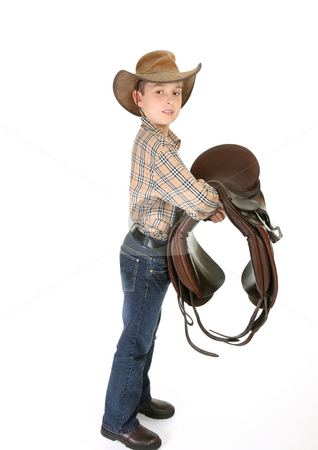 Horse rider with a saddle stock photo, A young horse rider holding a saddle. - side view by Leah-Anne Thompson