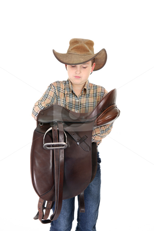 Rural boy holding a saddle stock photo, Country boy carrying a saddle by Leah-Anne Thompson