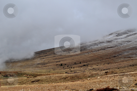 Mountain stock photo, A dry land covered by snow on the top of its mountains with a foggy weather by Tony Abdou