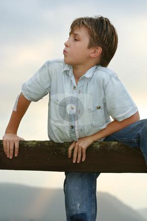 Boy climbing on a fence stock photo, Boy climbs up onto a fence. by Leah-Anne Thompson