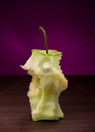 Eaten green apple stock photo, Eaten green apple on the wooden table, closeup shot against purple background by Vladimir Koletic