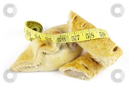 Sausage Roll with Pasty and Tape Measure stock photo, Single golden sausage roll cut in half with pasty and yellow tape measure on a reflective white background by Keith Wilson