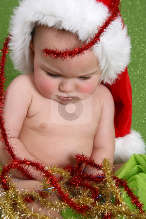 Christmas Baby stock photo, Christmas Baby playing with decorations on a green background by Vanessa Van Rensburg