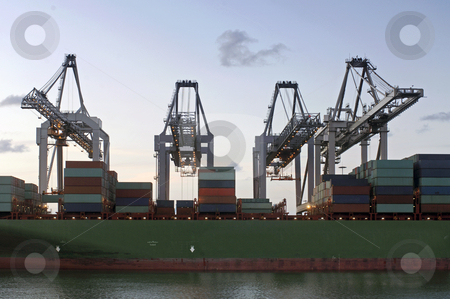 Unloading stock photo, Four huge cranes simultaneously unloading a container ship at dusk by Corepics VOF