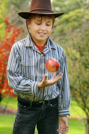 Healthy Living Healthy Eating stock photo, A boy standing in pristine countryside is throwing up a fresh organic red apple. eg:  green living, healthy lifestyle, organic produce, nature's best,  Special Note: motion in apple and hand, 400iso by Leah-Anne Thompson