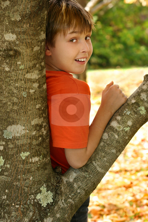 Boy leaning against a tree stock photo, A child leaning against the trunk of a deciduous tree in the Autumn by Leah-Anne Thompson
