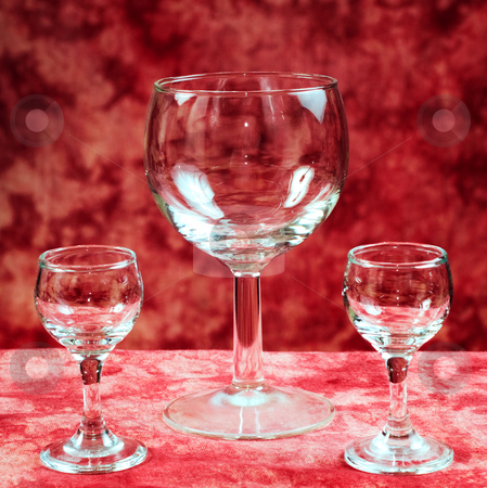 Goblets stock photo, Two small and one large glass goblets are empty against a red background by Richard Nelson
