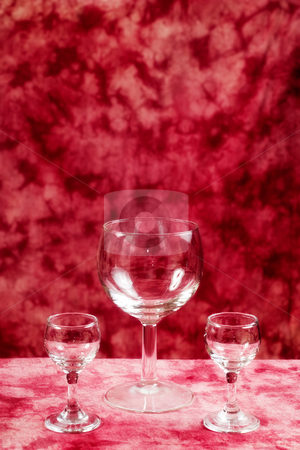 Romantic Drinks stock photo, Two small and one large glass goblets are empty against a red background by Richard Nelson