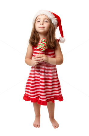 Little girl wearing santa hat and holding Christmas candy stock photo, A small girl wearing a santa hat and holding Christmas candy. by Leah-Anne Thompson