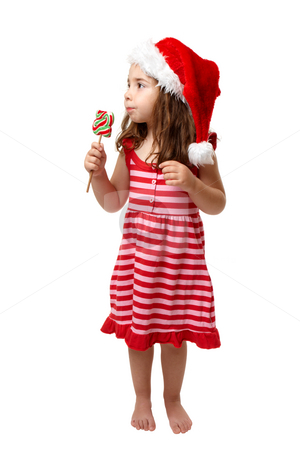 Christmas girl with candy stock photo, Christmas girl eating a lollipop candy in the shape of Christmas tree. by Leah-Anne Thompson