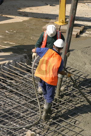 Commercial Cementing stock photo, Workers standing on thick steel mesh and pouring concrete through a large hose attached to a long extendable boom connected to a concrete hydraulic truck mounted pump..   There is motion in the pouring cement. by Leah-Anne Thompson