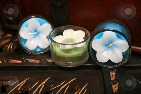 Three Candles stock photo, Three candles on a brown wooden surface by Vanessa Van Rensburg