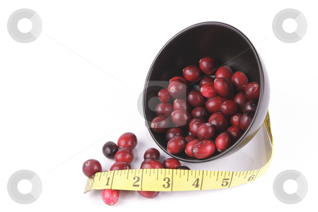 Cranberries spilling out of a Black Bowl with Tape Measure stock photo, Red ripe cranberries spilling out of a small round black bowl on its side with a tape measure on a reflective white background by Keith Wilson