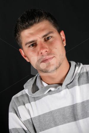 Male Model stock photo, Male model in studio against a dark wall by Vanessa Van Rensburg