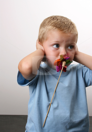 Dont want to hear stock photo, Toddler playing with a wind toy, holding his ears by Vanessa Van Rensburg