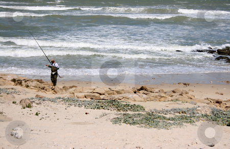 Fisherman on the rocks stock photo, Fisherman on the rocks checking out his equipment by Vanessa Van Rensburg