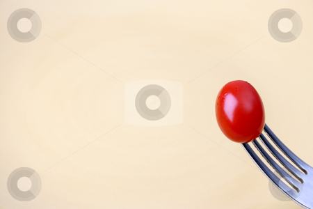 Single Tomato stock photo, Single tomato on a fork against a yellow plate by Vanessa Van Rensburg