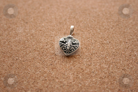 Silver Heart stock photo, Silver Heart Charm on a cork background by Vanessa Van Rensburg